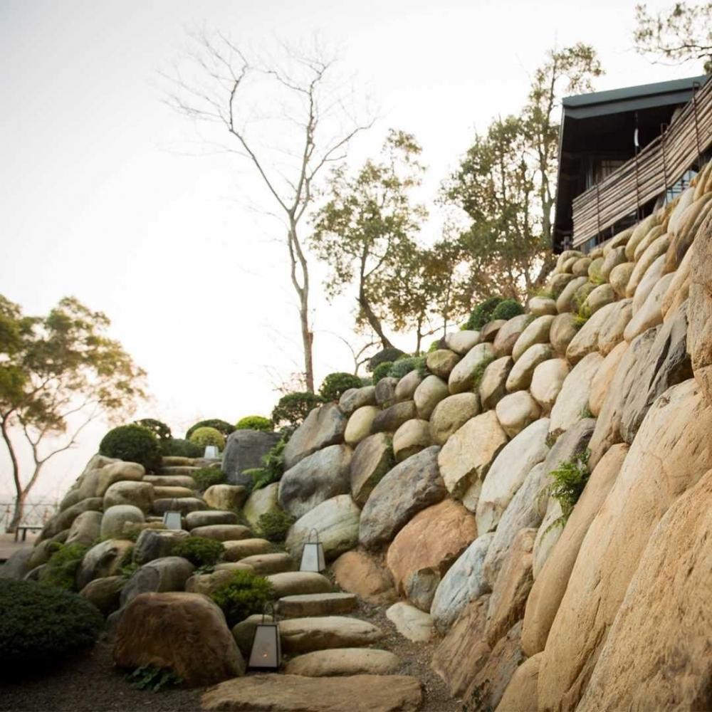 其中一面老石牆,由一塊塊石頭砌成,不切割、不打磨,只有靠著轉一轉角度,將石頭最平的一面運用土法堆疊呈現,曲面的設計,甚是典雅壯觀。